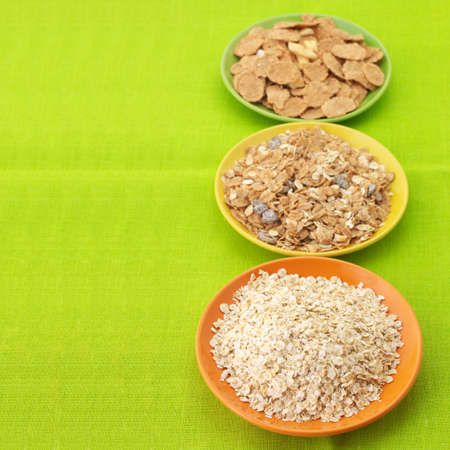 Various breakfast cereal in colorful plates on green tablecloth. photo