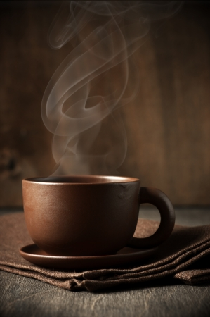 Cup of hot coffee with stem on wooden background.