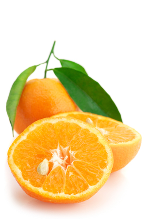 Whole and cut fresh tangerines with leaves isolated on white background. photo