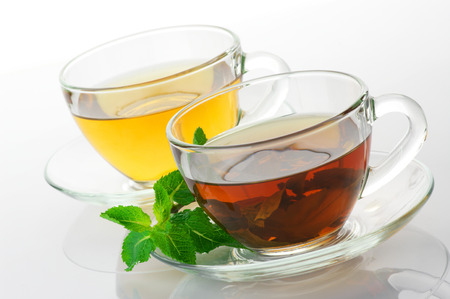 Cups of black and green tea with mint isolated on white background. photo