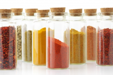Assorted ground spices in bottles on white background. photo