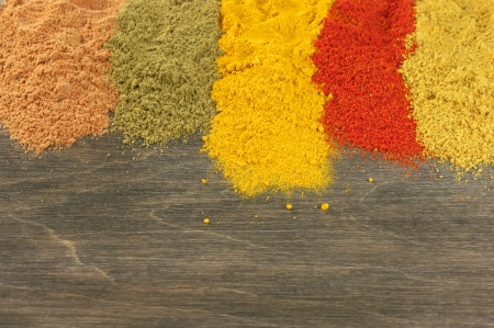 Assorted loose powder spices on wood. Top view point.