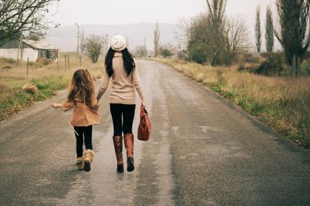 国の道路の上を歩いて彼女の小さな娘と若い母親。