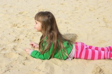Small cute girl lying on sand at beach. photo