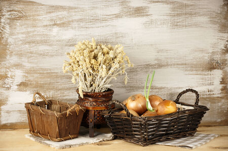 Wicker baskets with onion and dry flowers on rustic wooden. photo