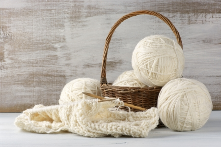 Natural woolen yarn and knitting on vintage wooden. photo