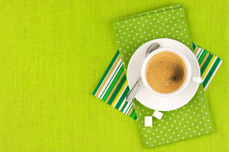 White cup of coffee on green linen. Top view. Stock Photo - 25644442