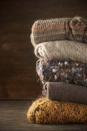 mohair: Stack of knitted sweaters on wooden background.
