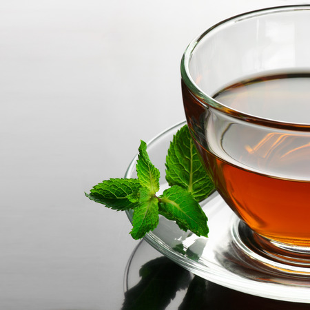 Glass cup of tea with mint close-up on glossy background. photo