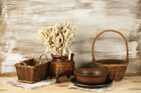 Wicker and ceramic utensil on rustic wooden background. photo