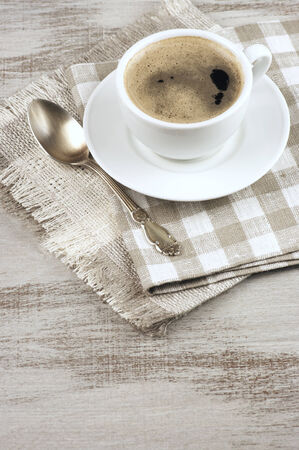 White cup of coffee on vintage wood.  photo