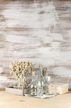 Glass bottles and dry flowers on rustic wooden background. photo