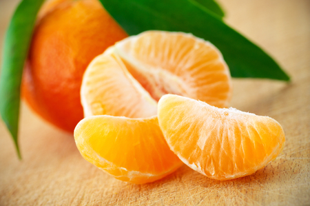 Close-up of fresh whole tangerine and slices on wood. photo