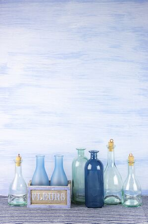 Collection of decorative bottles on blue wooden background. photo