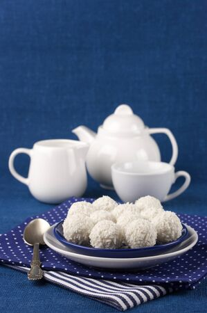 Coconut candies and tea in white dishware on blue cloth. photo