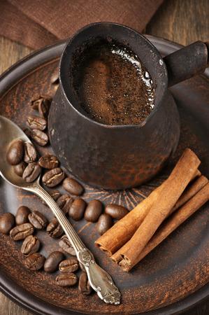 cezve: Fresh coffee in cezve on ceramic plate. Stock Photo