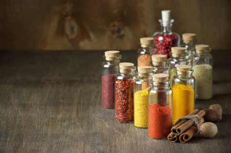 Assorted ground spices in bottles, cinnamon sticks and nutmeg on wood. photo