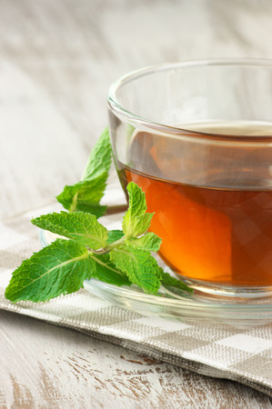 Glass cup of tea with mint on rustic table. photo