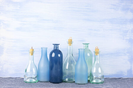 Collection of decorative bottles on blue wooden wall. photo