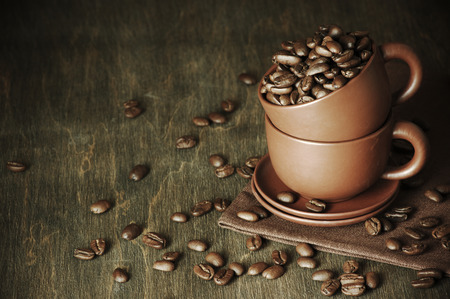Roasted coffee beans in ceramic cups on vintage wooden background. photo