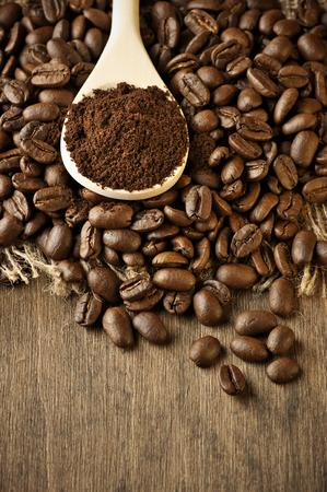 焼かれたコーヒー豆と織り目加工の木材で木のスプーンの挽いたコーヒー。 写真素材