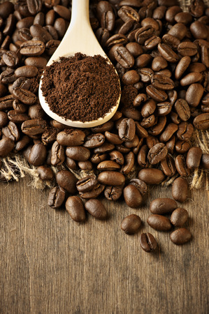 Roasted coffee beans and ground coffee in wooden spoon on textured wood. Stockfoto