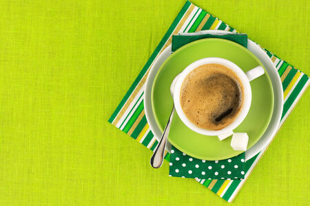 White cup of coffee on green linen. Top view. Stock Photo - 27118028