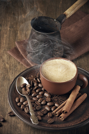 Cup of hot coffee, beans, cinnamon and cezve on vintage wooden background. photo