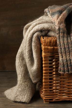 mohair: Fluffy knitted sweaters on wicker basket.