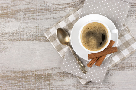 cinnamon: White cup of coffee on vintage wood. Top view.
