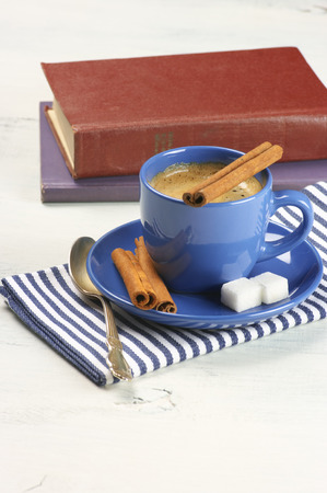 Blue cup of coffee and books on white vintage wood. photo