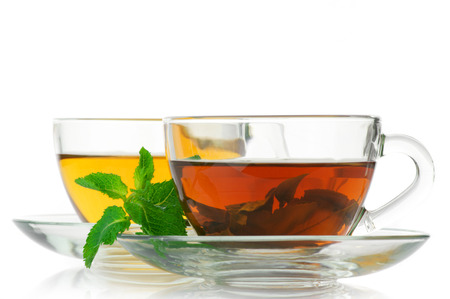 green and black: Cups of black and green tea with mint isolated on white background. Stock Photo