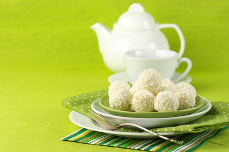 Coconut candies and tea on green cloth. photo