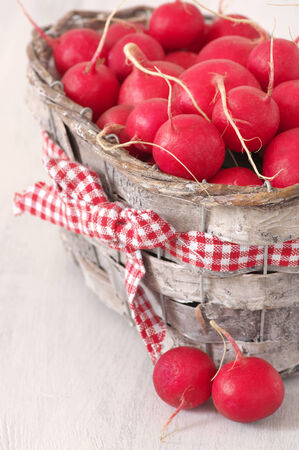 Radish in basket on wooden background. photo
