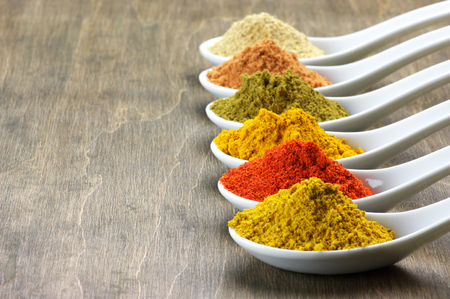 Assorted powder spices in white spoons on wood. photo
