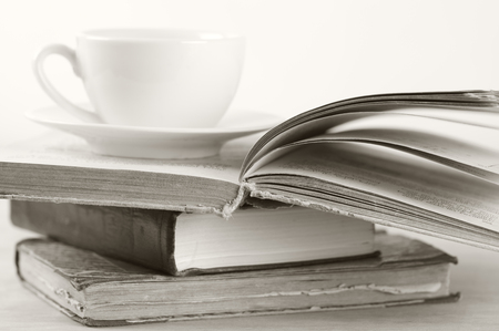 Stack of books and cup on wooden table. Shallow DOF, sepia. photo