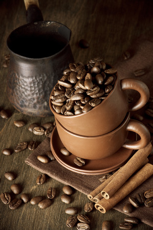 Coffee beans, cinnamon and cezve on vintage wooden background. photo