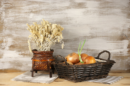 Wicker baskets with onion and dry flowers on rustic wooden background. photo