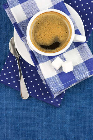 White cup of coffee on blue linen. Top view. photo