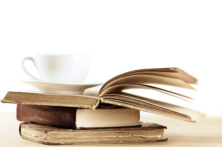 Stack of books and cup on wooden table. Shallow DOF. photo