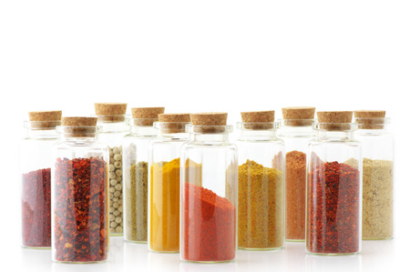 Assorted ground spices in bottles isolated on white background. photo