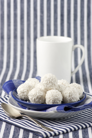 Coconut candies and tea on striped cloth. photo