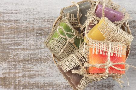 Assorted natural soaps in basket on vintage wood. photo