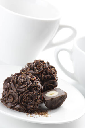 Homemade natural chocolate candies and cups on white background. photo