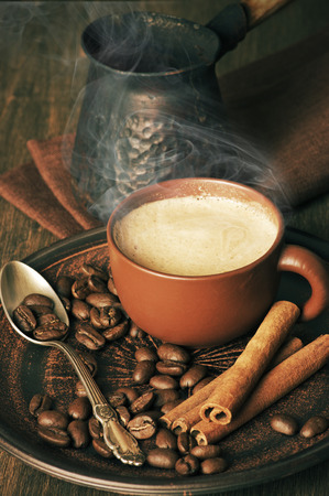 cezve: Cup of hot coffee, beans, cinnamon and cezve on vintage wooden background.