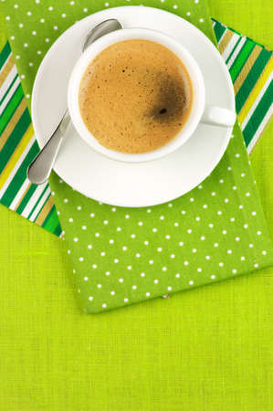 White cup of coffee on green linen. Top view. photo