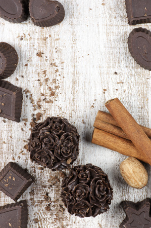 Homemade natural chocolate candies with ingredients on rustic wooden background. photo