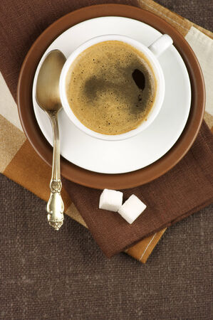 White cup of coffee on brown linen. Top view. photo