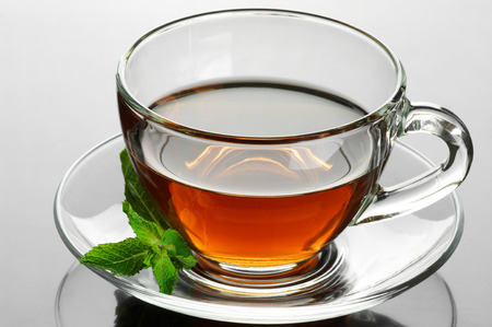 Glass cup of tea with mint on glossy background. photo