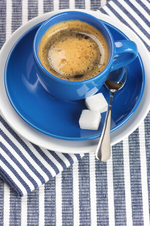 Blue cup of coffee on blue striped tablecloth. photo